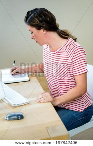 business woman at her desk writing in her planner