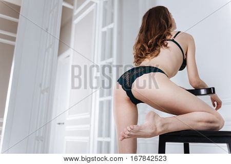 I have perfect body. Brunette girl wearing black lace lingerie holding her leg on the chair keeping her head upwards
