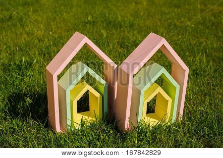 several colorful wooden houses on green grass
