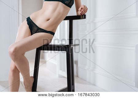 Beautiful silhouette. Slim girl wearing black underwear sitting on black chair while leaning on back of seat