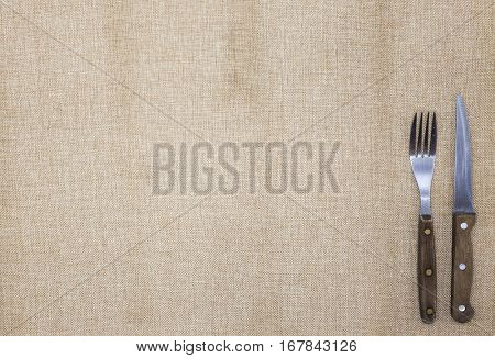 Tablecloth of burlap, fork,knife for steak and napkin . Is used to create a menu for the steak restaurant.The background for the menu.