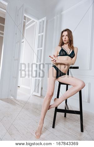 Be afraid of me. Enigmatical slim brunette wearing black lace lingerie sitting on black chair while posing in white studio
