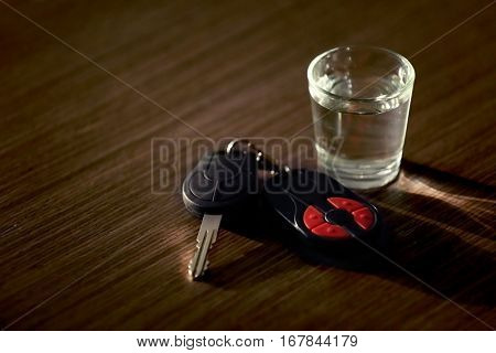 Glass with alcoholic beverage and car key on table. Don't drink and drive concept