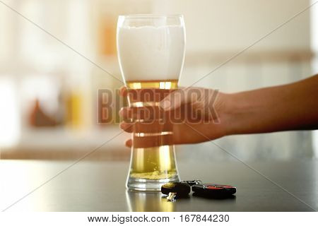 Female hand with glass of beer and car key on table. Don't drink and drive concept