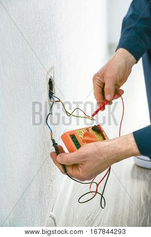 Electrician measuring earth resistance prior to installation of new socket, closeup