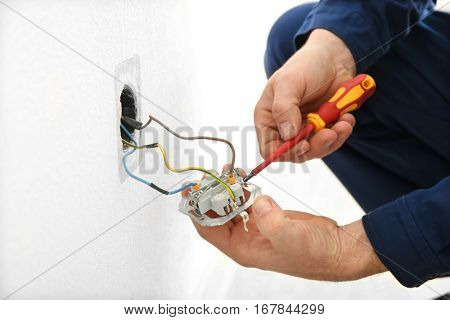 Electrician disassembling wall socket in new building, closeup