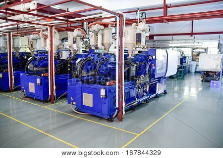 Row of plastic injection machines at emty clean workshop