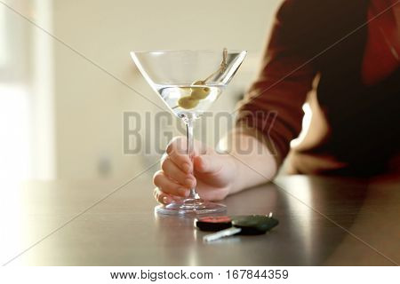 Woman sitting at table with glass of alcoholic beverage and car key, closeup. Don't drink and drive concept