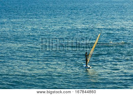 Windsurfer in the sea, man on windsurf conquering the waves