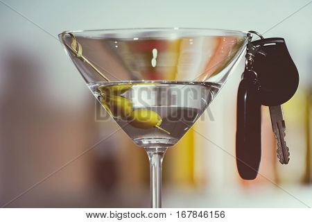 Glass of alcoholic beverage and car key on blurred background, closeup. Don't drink and drive concept