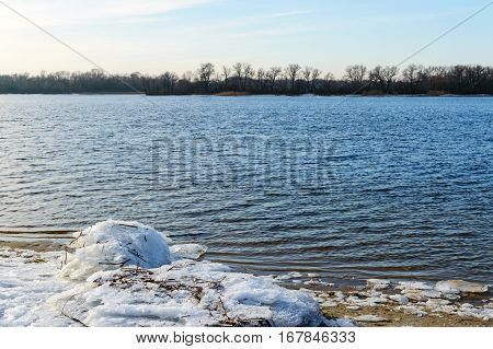 Winter landscape. A view of the wide river. On an empty shore - chunks of ice. Cold season. Clear day.