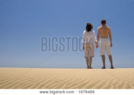 Young Couple Holding Hands On The Beach In Gran Canaria