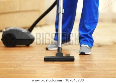Close up of man hoovering floor with vacuum cleaner