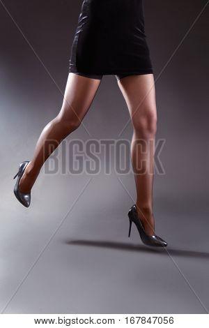 Beautiful woman legs in black stockings on grey background