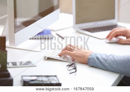 Hands of programmer working with computer in office