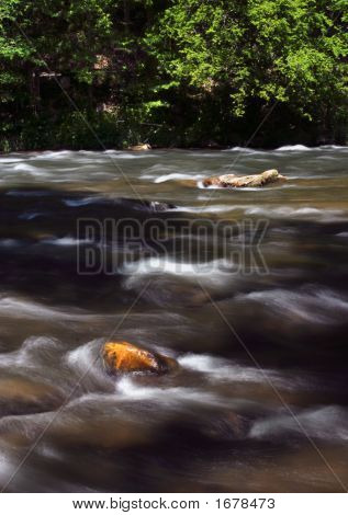 The cool waters of the Nantahala River in North Carolina rush swiftly by exposed rocks. poster