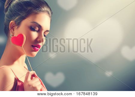 Beauty joyful Young fashion model Girl with Valentine Heart shaped cookie on stick in her hand. Love Concept. Beautiful seductive young woman. Valentines Day gift. Over grey background with hearts