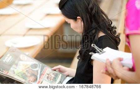 people looking menu waitress taking order restaurant