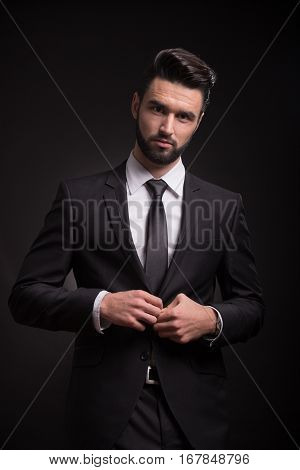 One Young Man Serious Looking Camera Suit Buttoning