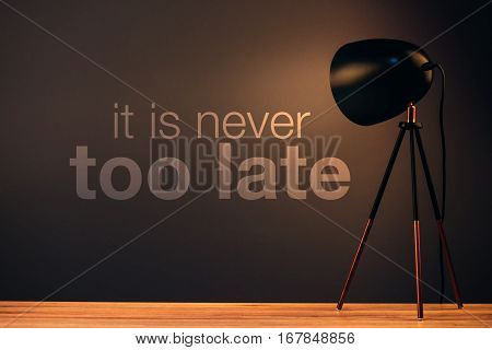 It is never too late motivational quote message on office wall behind desk illuminated by the lamp