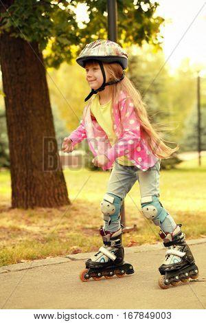 Cute little girl on roller skates in park
