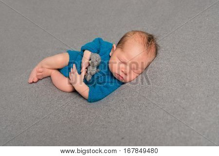 Tired baby in a blue costume napping after a tough day, hugging a teddy