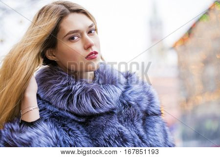 Portrait of a beautiful young blonde woman in a blue fur coat, winter street outdoors