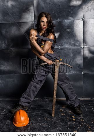 sexy female miner worker with pickaxe, in coveralls over his naked body. erotic industry concept.