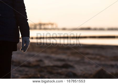 Arm and body detail of unrecognizable walking woman at cold winter beach sunset time (copy space)