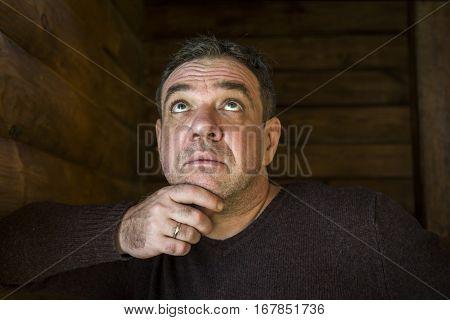 Portrait of pensive sad middle-aged men. He looks up.