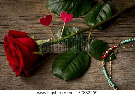 Red rose hearts and bracelet bijouterie on a table