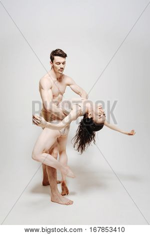 Romantic atmosphere. Graceful charming young dancers standing in front of the white wall and expressing gracefulness while touching each other