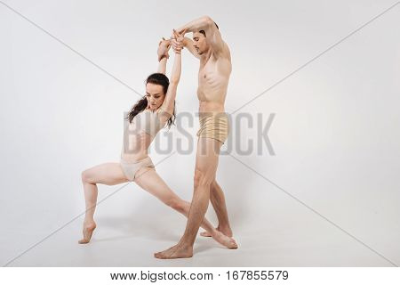 Flexible dancers stretching. Pleasant flexible powerful gymnasts dancing against white background and expressing tenderness and elegance while stretching