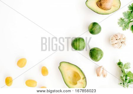 Raw food ingredients of guacamole: avocado coriander cherry tomato lime garlic. Flat lay top view. Food concept.