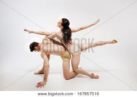 Immobilized body sculpture . Graceful muscular involved ballet dancers performing in the white colored studio and showing their flexibility while posing
