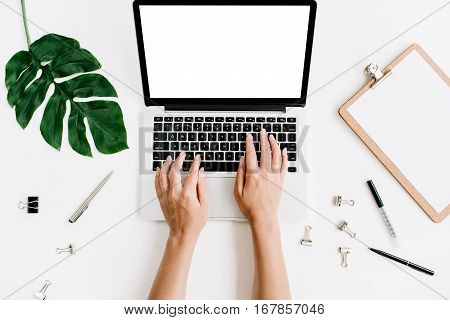 Workspace with hands typing on laptop with blank screen. Flat lay top view