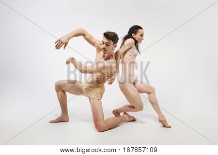 Control your body. Graceful muscular unemotional ballet dancers performing in the white colored studio and demonstrating their flexibility while posing