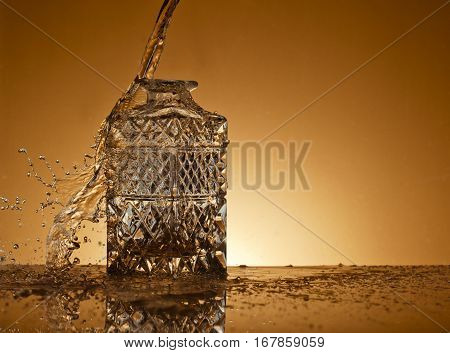 Decanter and and flying droplets on a gold background