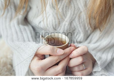 A girl in a light knitted sweater warming his hands on a cup of tea. Photo girl with no face only his hands against the backdrop of a sweater.