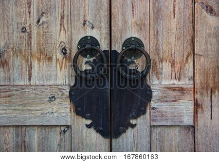 Old wooden door and wrought-iron handle. Ancient door handle. Forged door knocker.