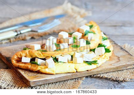 Delicious tofu omelette with parsley. Home roasted omelette stuffed with tofu and parsley on a wooden board. High protein breakfast. Fork and knife on old wooden table. Closeup