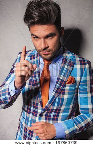 elegant man in checkered suit gesturing for you to behave or to have your attention
