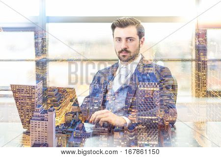 Portrait of successful corporate businessman in bright modern office with laptop computer looking at camera. New Your city lights reflection in window. Business concept.