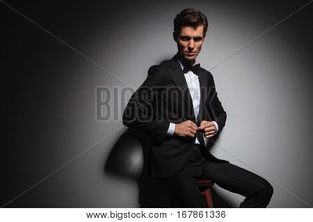 seated elegant business man in tuxedo buttoning his coat and looks at the camera