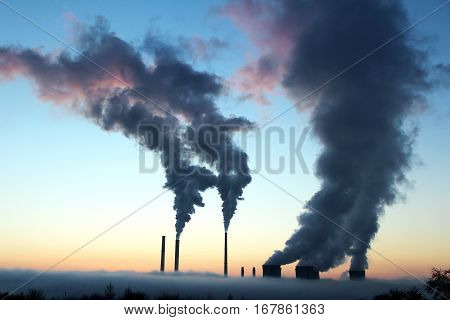 emission from brown coal power plant during the sunset