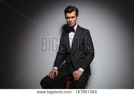 successful elegant man in tuxedo and bowtie sitting on stool and looks at the camera , studio picture on grey background