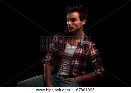 side view of an angry guy sitting on a chair against black studio background
