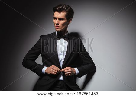 attractive young man in tuxedo and bowtie buttoning his coat and looks to his side, standing in studio against grey background