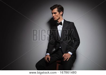 side view of a seated man wearing tuxedo and bowtie, studio picture with copyspace