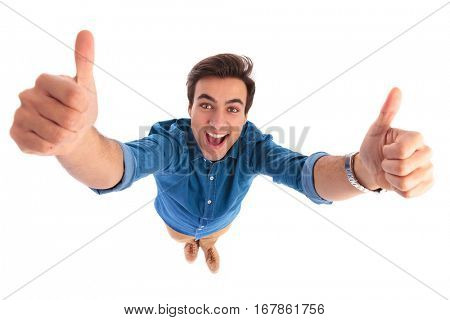 super excited young casual man screaming while making the ok thumbs up hand sign on white background, wide angle picture